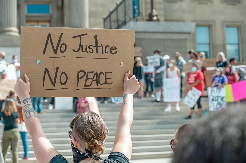 protestors holding no justice no peace sign